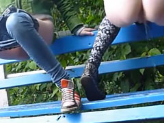 Pissende Mädchen auf der Parkbank