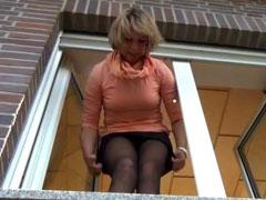 Hausfrau pisst aus ihrem Fenster